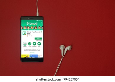Los Angeles, January 11, 2018: Smartphone with Bitmoji application in google play store on red background with earphones plugged in and copy space