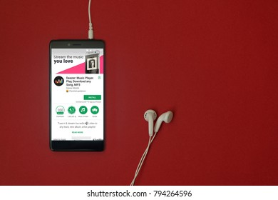 Los Angeles, January 11, 2018: Smartphone with Deezer application in google play store on red background with earphones plugged in and copy space