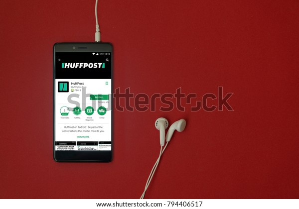 Los Angeles, January 11, 2018: Smartphone with Huffpost application in google play store on red background with earphones plugged in and copy space