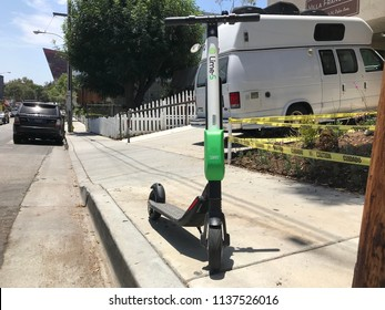LOS ANGELES, JULY 11TH 2018: A Lime scooter stands abandoned on the sidewalk on Palm Ave in West Hollywood. The city recently voted to ban the devices from being left unattended around town.