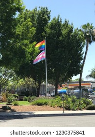 LOS ANGELES, July 24th, 2018: Flag pole with the LGBTQ rainbow flag (top) and transgender flag (bottom) waving in the wind inside a park in West Hollywood, California, symbolizing gay pride.