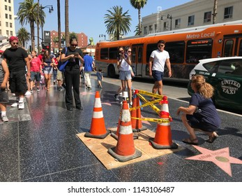 LOS ANGELES, JULY 26, 2018: A woman poses next to traffic cones on top of President Donald Trump's star on the Hollywood Walk of Fame on Hollywood Boulevard, after it was vandalized on July 24, 2018.