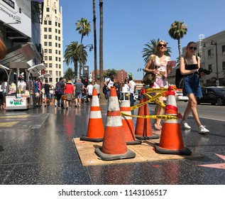 LOS ANGELES, JULY 26, 2018: Two women walk past the traffic cones on top of President Donald Trump's star on the Hollywood Walk of Fame on Hollywood Boulevard, after it was vandalized on July 24, 2018