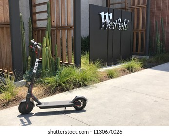 LOS ANGELES, JULY 7TH 2018: A Bird scooter stands abandoned on the sidewalk in front of the Westfield shopping mall on Santa Monica Boulevard in Century City.