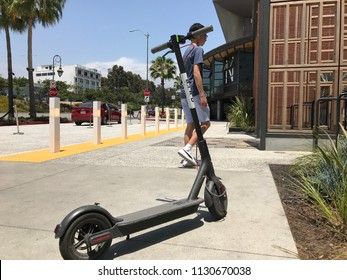 LOS ANGELES, JULY 7TH 2018: Low angle close up of a Bird scooter standing abandoned on the sidewalk in front of the Westfield shopping mall in Century City, with man walking past in the background.