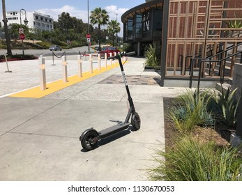 LOS ANGELES, JULY 7TH 2018: Wide shot of a Bird scooter standing abandoned on the sidewalk in front of the Westfield shopping mall on Santa Monica Boulevard in Century City.
