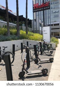 LOS ANGELES, JULY 7TH 2018: Two Bird scooters stand abandoned among bikes at a bike rack in front of the Westfield shopping mall on Santa Monica Boulevard in Century City.