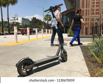 LOS ANGELES, JULY 7TH 2018: Low angle close up of a Bird scooter standing abandoned on the sidewalk in front of the Westfield shopping mall in Century City, with two people in walking in background.