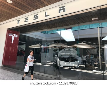 LOS ANGELES, JULY 7TH 2018: A woman walks past the Tesla car dealership at the Westfield shopping mall in Century City. CEO Elon Musk's company has been plagued by production delays.