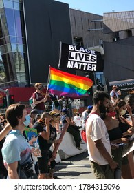 LOS ANGELES, June 14th, 2020: Black Lives Matter BLM protest on Hollywood Blvd Walk of Fame. Protesters with face masks carrying Black Lives Matter and LGBTQ rainbow flags walk past Chinese Theater.