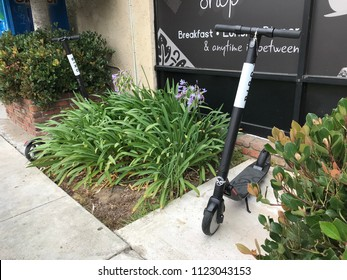 LOS ANGELES, JUNE 16, 2018: Two Bird scooters stand abandoned on a sidewalk in Culver City, California.