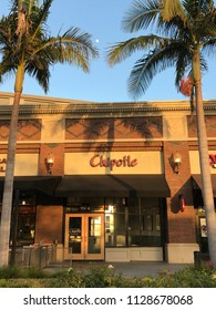 LOS ANGELES, JUNE 23RD 2018: Exterior wide shot of Chipotle restaurant in Downtown Culver City in the late afternoon sun, with full moon between two palm trees shining from above.