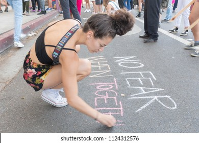 Los Angeles, June 30, 2018: An activist writing on the floor during The Families Belong Together march around the Metropolitan Detention Center