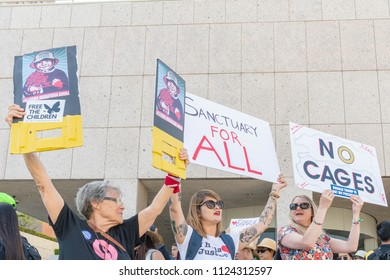 Los Angeles, June 30, 2018: Activists hold signs  during The Families Belong Together march around the Metropolitan Detention Center