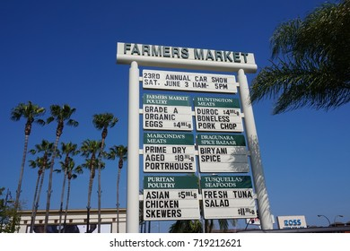 LOS ANGELES, JUNE 3RD, 2017: A large Farmers Market sign outside the famous Original Farmers Market on Third and Fairfax near The Grove shopping center, against a blue sky, surrounded by palm trees.