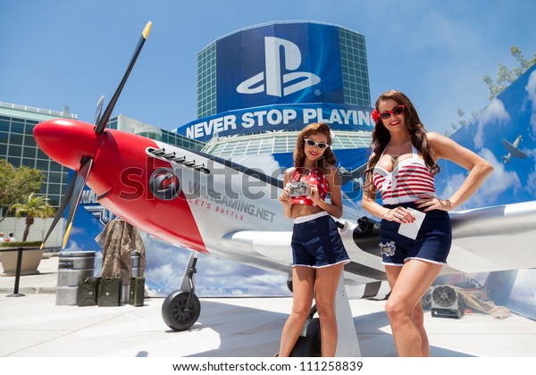LOS ANGELES - JUNE 8: Pin ups posing for media at the entrance of the show with PlayStation sponsorship in the background during E3 2012, world video games Expo June 8, 2012 in Los Angeles, CA