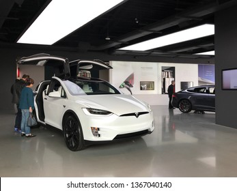 LOS ANGELES, March 30th, 2019: Customers inspect a white Tesla with open wing doors on display inside the showroom at the Tesla store inside the Westfield shopping mall in Century City.