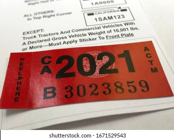LOS ANGELES, March 5th, 2020: Department of Motor Vehicles DMV California registration tag sticker attached to renewal notice side angle extreme close up.