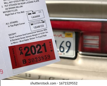 LOS ANGELES, March 5th, 2020: Department of Motor Vehicles DMV California registration tag sticker attached to renewal notice next to partial license plate on old car close up.