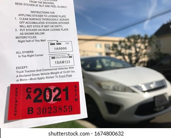 LOS ANGELES, March 5th, 2020: Department of Motor Vehicles DMV California registration tag sticker attached to renewal notice, next to a parked white luxury car in a residential neighborhood.
