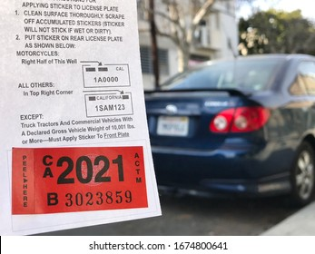 LOS ANGELES, March 5th, 2020: Department of Motor Vehicles DMV California registration tag sticker attached to renewal notice close up, next to the back of a parked blue Toyota car.