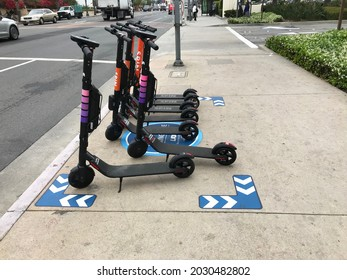 LOS ANGELES - MAY 15, 2019: Electric Lyft and SPIN scooters ready for rent on a Los Angeles sidewalk.