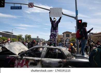LOS ANGELES - MAY 30, 2020: Unidentified Participants Standing On Burned Police Car During The Protest March Against Police Violence Over Death Of George Floyd.