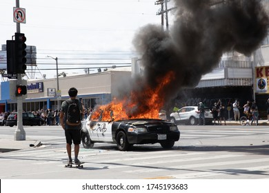 LOS ANGELES - MAY 30, 2020: Unidentified Participant Of Protest March Against Police Violence Over Death Of George Floyd Taking Picture of Burning Police Car.