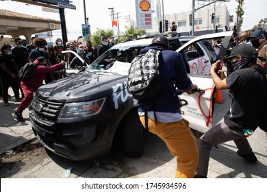 LOS ANGELES - MAY 30, 2020: Unidentified Participants Vandalizing Police Car During The Protest March Against Police Violence Over Death Of George Floyd.