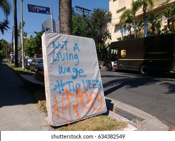 LOS ANGELES, MAY 4TH, 2017: Close up of a large protest sign in a Hollywood neighborhood, written on an old mattress, declaring rideshare company Uber does not pay a living wage, referring to Twitter.