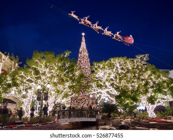 LOS ANGELES, NOV 26TH, 2016: Bright Christmas lights reflect in the fountain of the Grove shopping center, as Santa Claus and his reindeers appear to fly above it and its 100-foot-tall Christmas tree.
