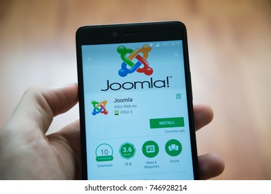 Los Angeles, november 2, 2017: Man hand holding smartphone with Joomla application in google play store