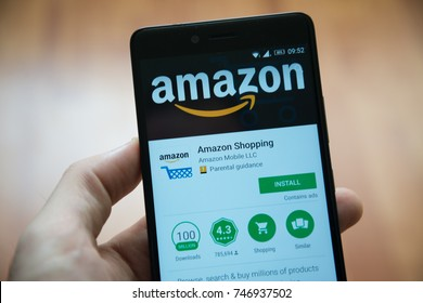 Los Angeles, november 2, 2017: Man hand holding smartphone with Amazon shopping application in google play store