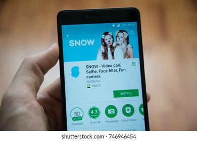Los Angeles, november 2, 2017: Man hand holding smartphone with Snow application in google play store