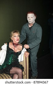 "LOS ANGELES - OCT 30:  Donna Keegan & ""Michael Myers"" Costumed Guest  arrive at the sCare Foundation Halloween Launch Benefit at Conga Room - LA Live on October 30, 2011 in Los Angeles, CA"