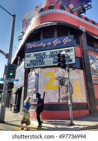 LOS ANGELES, OCT 7TH 2016: A musician stands in the shadow of Bob Marley's image on the facade of the Whisky a Go Go club on the Sunset Strip in Hollywood, a launching pad for bands such as The Doors.