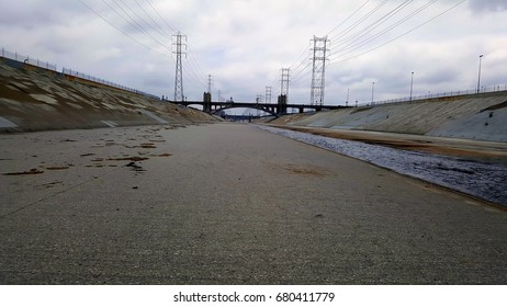 The Los Angeles river with bridge and blue sky in the background.