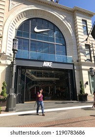 LOS ANGELES, SEP 22, 2018: A woman on her cell phone stands in front of the Nike store at the Grove shopping mall at Third and Fairfax in Los Angeles.