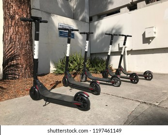 "LOS ANGELES SEP 28, 2018: Several controversial Bird scooters are parked in a neat row right underneath a ""No Parking"" warning sign."