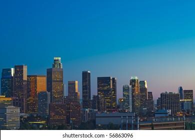 Los Angeles skyline at dusk with blue night sky.