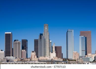Los Angeles skyline on a sunny day with blue sky.