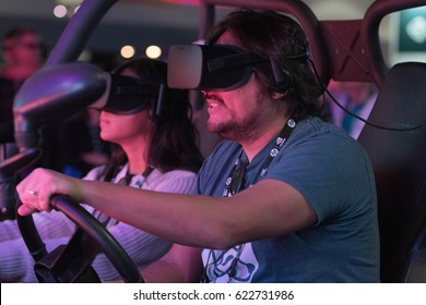 Los Angeles, USA - April 15, 2017: Man driving in virtual reality wearing futuristic VR headset during the VRLA Expo - Virtual Reality Exposition, at the Los Angeles Convention Center.