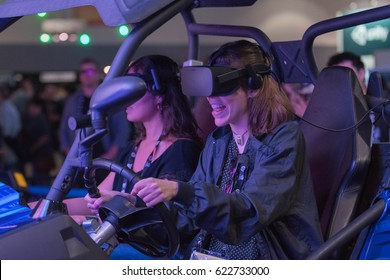 Los Angeles, USA - April 15, 2017: Smile happy woman getting experience using VR headset glasses of virtual reality on display during the VRLA Expo - Virtual Reality Exposition