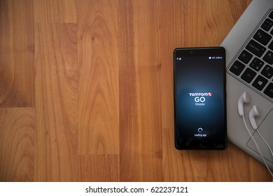 Los Angeles, USA, april 16, 2017: Tomtom Go application on smartphone with earphones and notebook on wooden background.