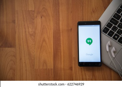 Los Angeles, USA, april 16, 2017: Google hangouts application on smartphone with earphones and notebook on wooden background.