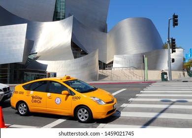 LOS ANGELES, USA - APRIL 5, 2014: Taxi cab drives by Walt Disney Concert Hall in Los Angeles. The famous landmark was designed by Frank Gehry.