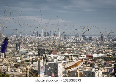 Los Angeles, USA - August 1, 2018: Old and rusty barbed wire fence, with lots of different objects attached to it, with downtown Los Angeles in the background, on a gloomy summer day.