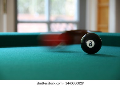 Los Angeles, USA - August 7, 2018: 8 ball on a green pool table, with a blurry red ball rolling past it, with a window and bright light in the background.