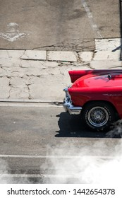 Los Angeles, USA - August 7, 2018: Front end of a beautiful classic red Ford Thunderbird, with smoke coming from the rear tyres, on a bright and sunny summer day.