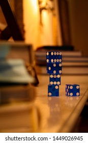 Los Angeles, USA - August 7, 2018: Blue straight cut razor edge dice, stacked on a wooden living room table, with books, a picture frame and lamps in the background, giving off warm light.